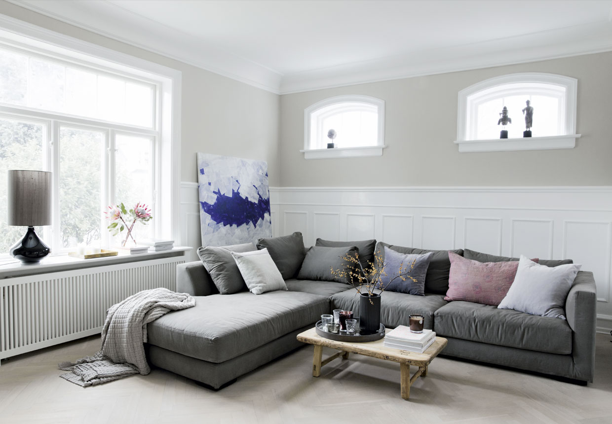 Gray sofain a Scandinavian interior  with lot of art and decor