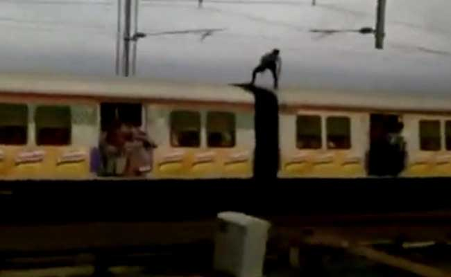 A man has been caught on camera performing death-defying stunts on top of a running Mumbai local.  A video, which has gone viral, shows him ducking the catenary steel rods, which support the overhead electricity lines.  He is seen standing on top of the running rain and ducking just in time as steel rods get close.  The overhead electricity lines supply 25,000 volts of current and the man is just a second away from a gruesome death.