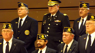 Veterans in uniform at attention during veterans day program