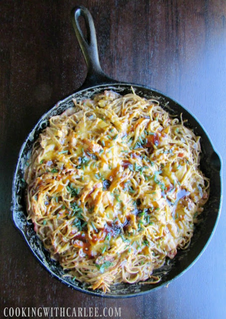 cast iron skillet full of bbq pulled pork spaghetti with melted cheese and herbs on top