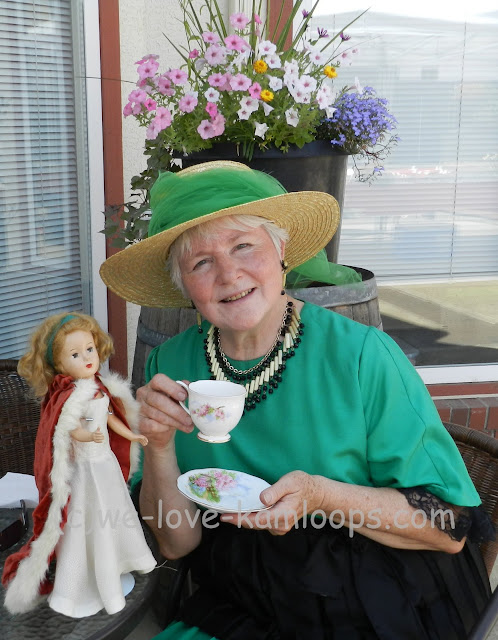 Val poses with a cup and her doll