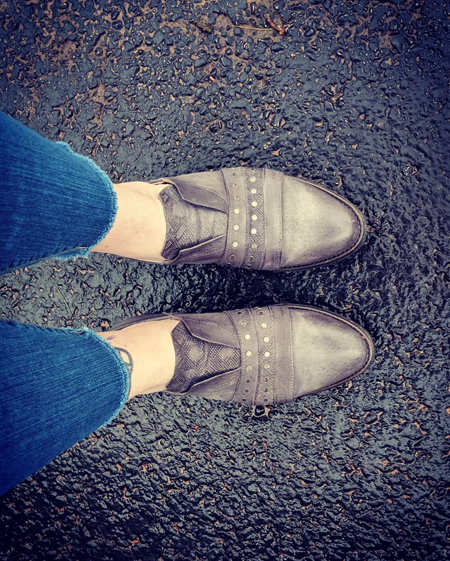 image of my feet standing on black pavement, wearing grey, no-lace oxfords