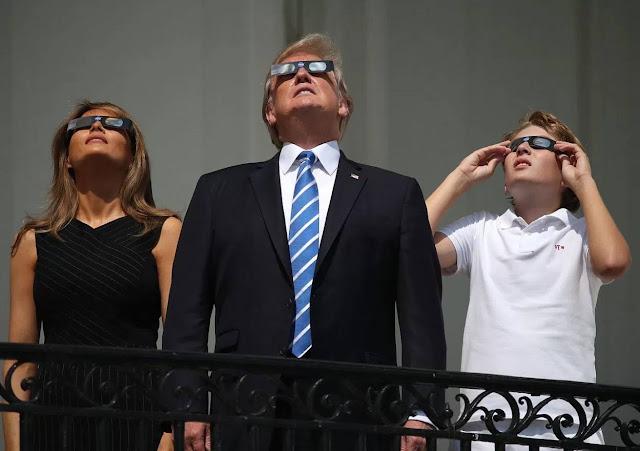 Tổng thống Donald Trump, Đệ nhất phu nhân Melania Trump, cùng con trai Barron Trump, đang ngắm nhật thực qua kính quan sát chuyên dụng bởi NASA từ ban công Truman, lầu 2 của văn phòng hành chính tòa Bạch Ốc, hướng nhìn ra bãi cỏ phía nam. Hình ảnh: Mark Wilson/Getty Images.
