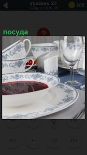 На столе лежит и стоит посуда, в тарелке налита жидкость, видимо суп