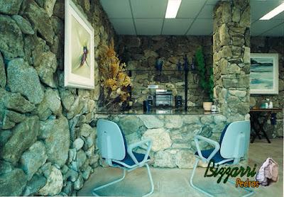 Revestimento com pedra moledo na parede, com esse tipo de colocação de pedra rústico, com a mesa de vidro, em escritório de empresa em Cotia-SP.