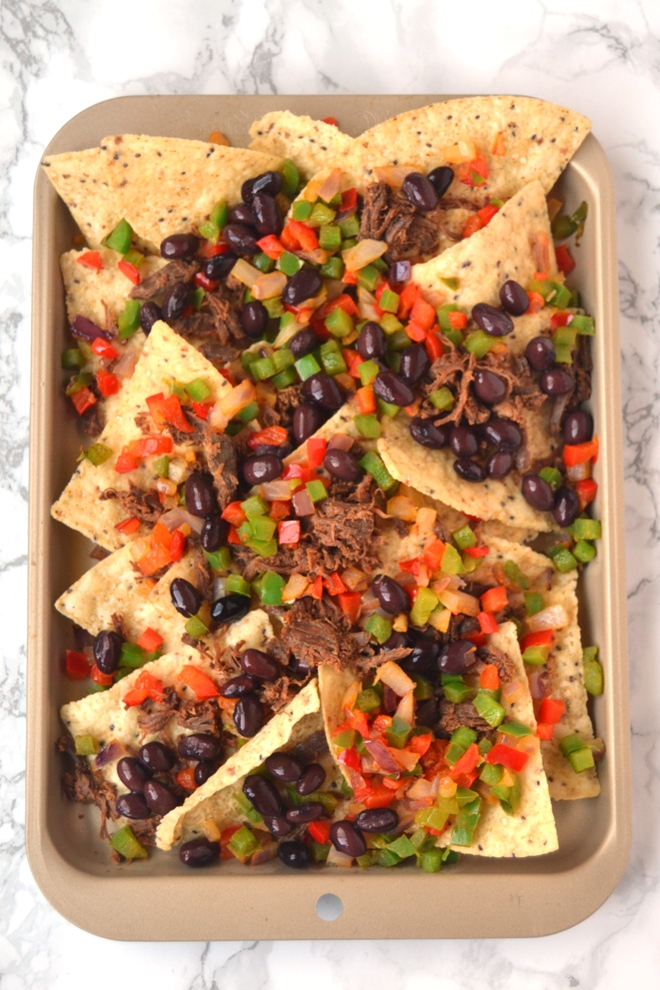 Loaded Sheet Pan Nachos come together in 15 minutes and are packed with sauteed black beans, bell peppers, melted cheese, jalapenos, corn, cilantro, tomatoes and shredded steak! www.nutritionistreviews.com