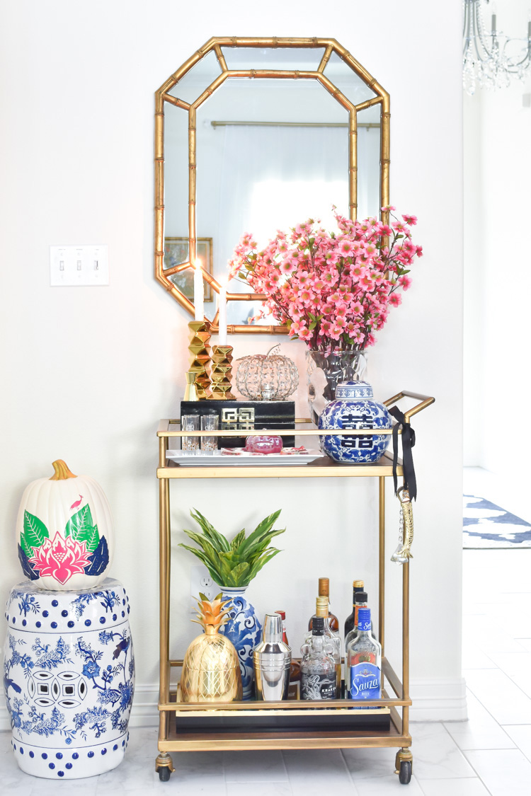 Vintage gold gilt bamboo mirror over a bar cart with fall and chinoiserie decor. #barcart #goldbarcart #entertaining