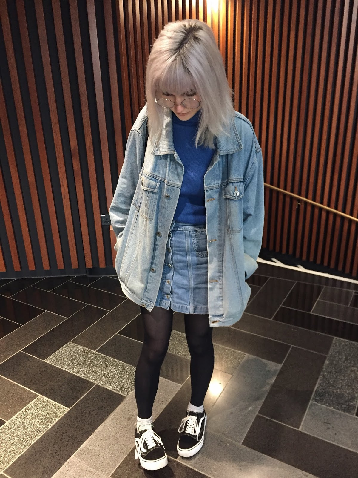 silver haired girl in denim jacket, denim skirt, vans and round glasses