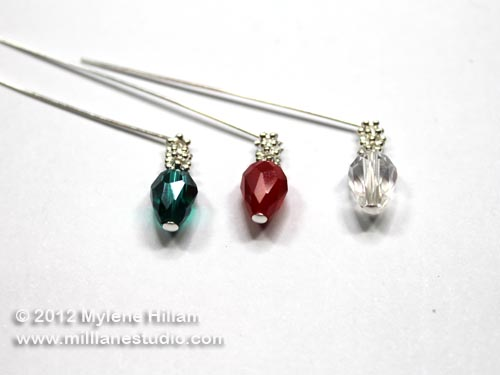 Green, red and clear teardrop crystal strung on 3 silver head pins with daisy spacers to create bud lights.