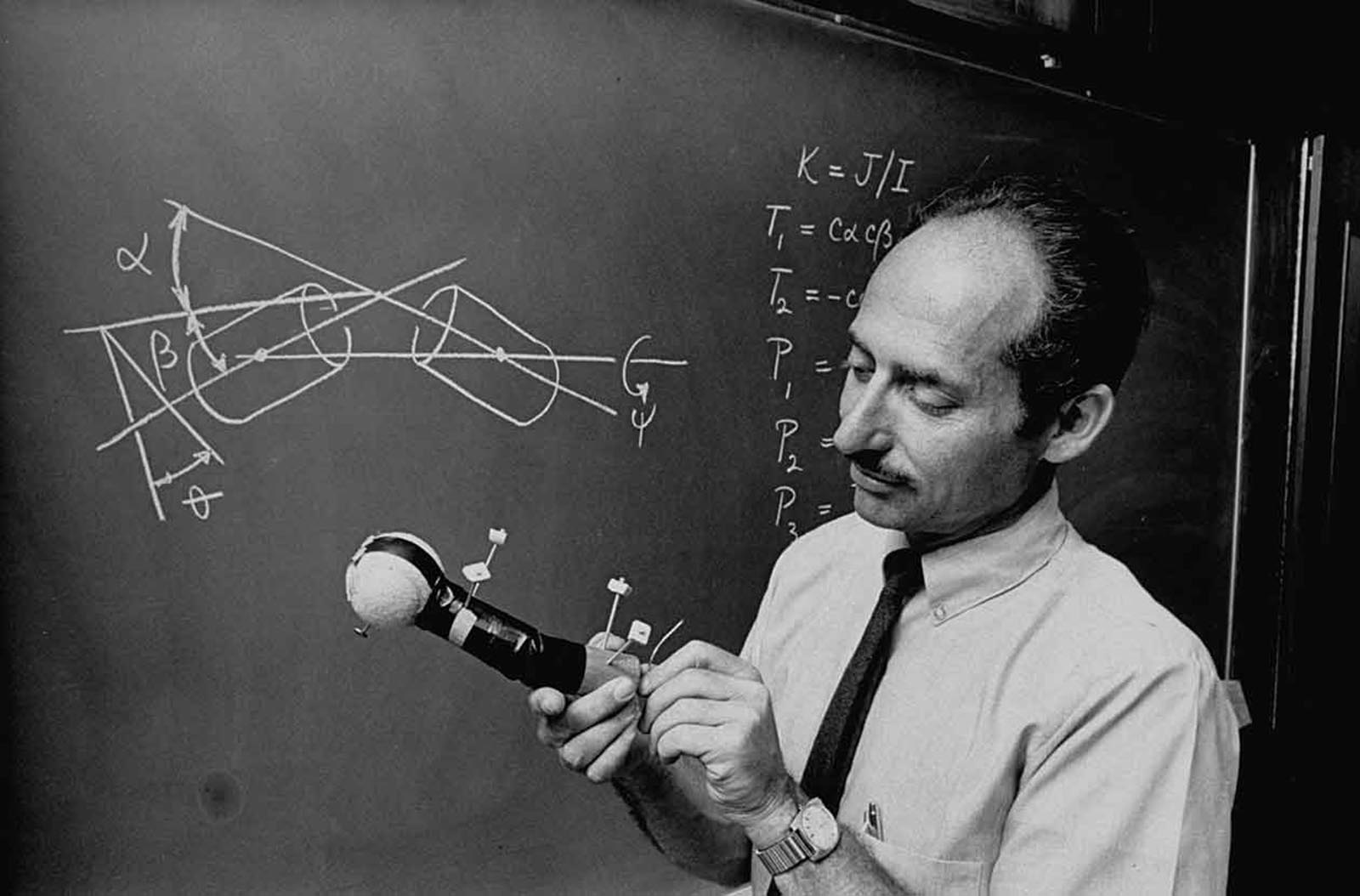 Professor Thomas R. Kane demonstrating a formula which explains how a cat's movements can be imitated by astronauts in space.