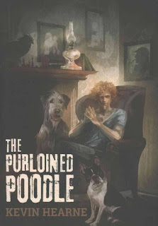Painted cover of The Purloined Poodle. An enormous grey Irish Wolfhound sits beside a red-haired white man who sits in an armchair with his fingers steepled. A Boston Terrier sits on the other side of the chair. Behind the group is a mantlepiece and a wall hung with paintings of Sherlock Holmes and a French Poodle.