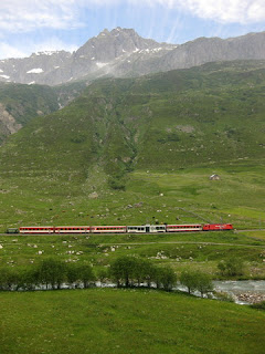 Red Swiss train crossing along the valley floor near Hospental, Switzerland