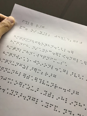 a page showing braille printed in ink