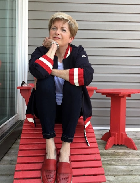 woman in jeans, white tee and navy baseball jacket sitting in a red Adirondack chair
