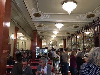 espaço da Versailles com lustres, espelhos e pessoas