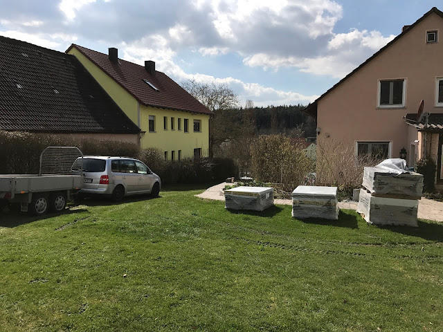 Palette mit Terrassenplatten stehen in der Wiese und der Bagger kommt  (c) by Joachim Wenk