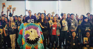 group of Tanaya's students holding her book and an eagle star quilt