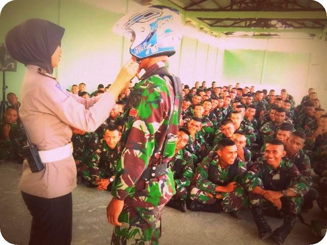 Kasat Lantas Polres MTB, AKP Marita Dyah Anggraini saat memasangkan helm kepada anggota Yonif 734