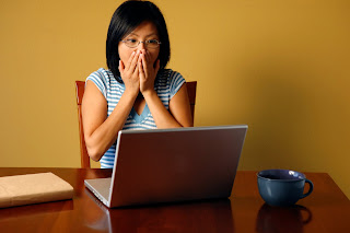Photo of a women looking frightened as she looks into a computer screen