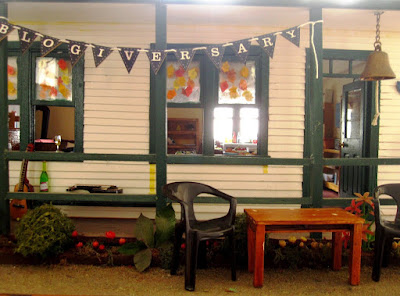 One-twelfth scale miniature school house exterior with a bunting strung across the verandha spelling out 'blogiversary'. Chairs and a table are set up outside the school, while on the veranda is a guitar, a ukulele, a bottle fo wine and a wine glass.