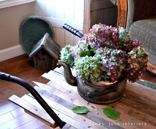 A vintage kettle becomes a flower vase for a unique wheelbarrow turned coffee table! Click to learn how!