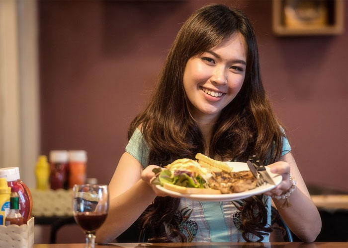 mulher mostrando um prato bem gostoso que ela fez