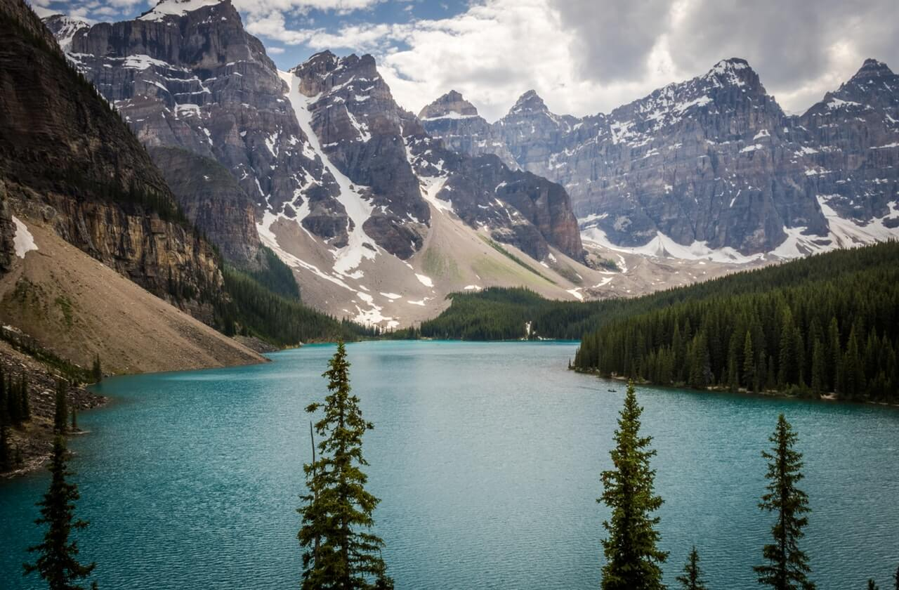 Body of Water Between Trees and Mountain at Daytime HD Copyright Free Image