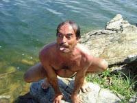 Lustiger Mann posiert am Wasser mit herausgestreckter Zunge