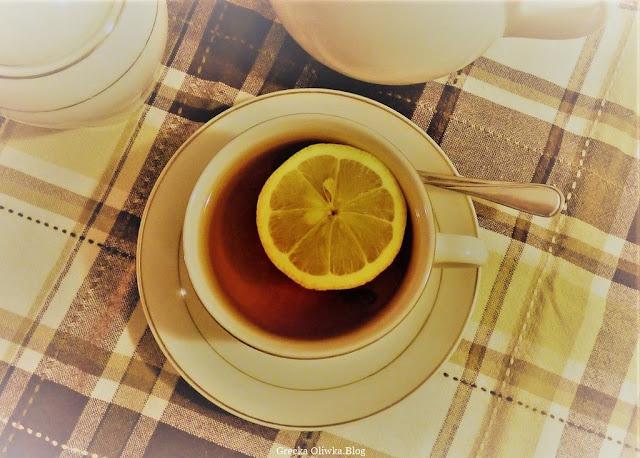 na stole kraciasta serweta oraz filiżanka herbaty z plastrem cytryny