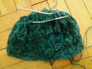 A cowl in the round knit in a lace leaf pattern, and dark turquoise fingering-weight yarn.