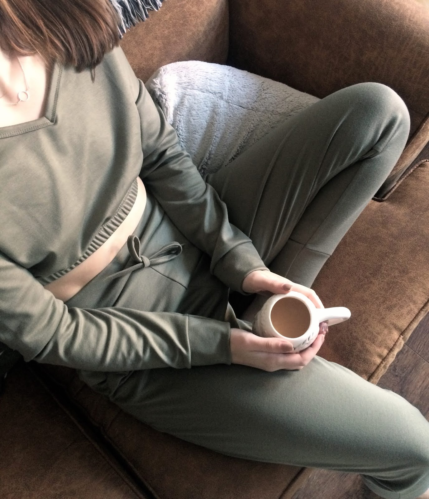 Holding a cup of tea, wearing comfy khaki loungewear set