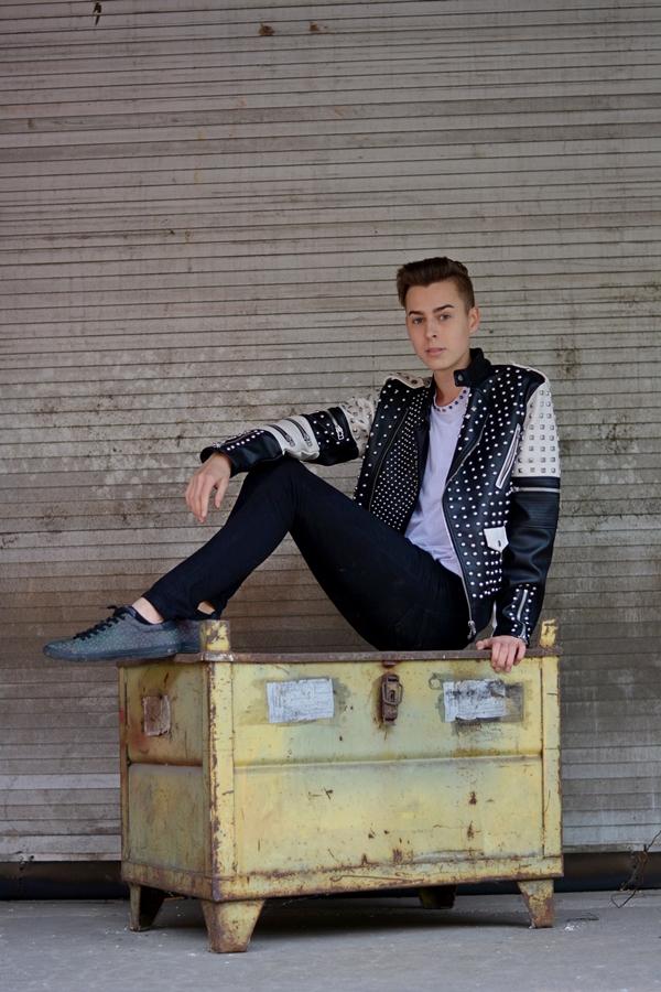 Junge sitzt auf Truhe vor Tor