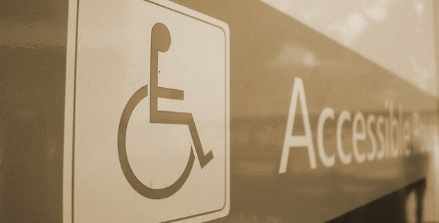 "Amber tinted glass sign with wheelchair symbol and the word ""Accessibility"""