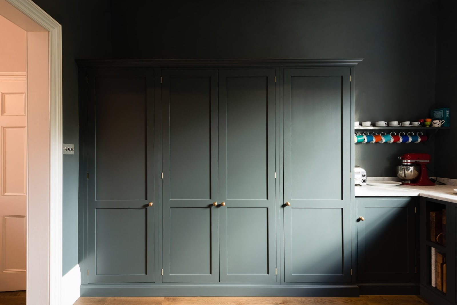 Dark blue-grey cabinets and walls in a luxurious classic London kitchen - found on Hello Lovely Studio