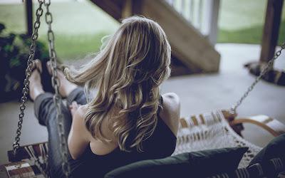 Chica rubia sentada en banco que se mueve