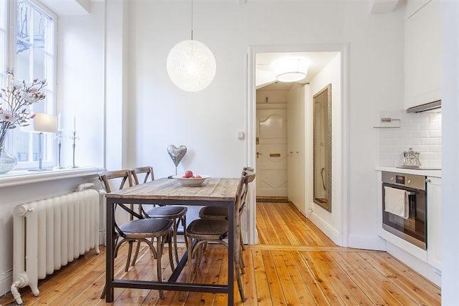 Comedor de un piso pequeño con sillas y mesa de madera y hierro