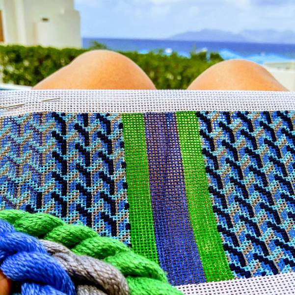 Anne stitching a clutch bag needlepoint canvas on holiday