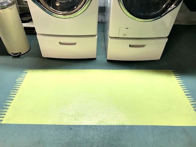 Painted area rug in front of washer and dryer