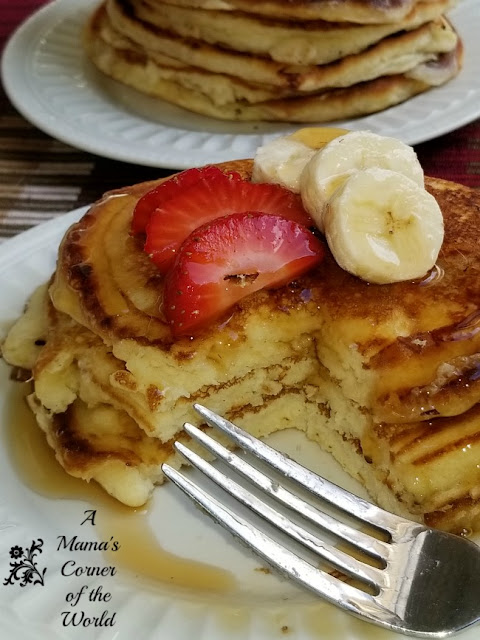 Stacks of pancakes with sliced strawberries and bananas