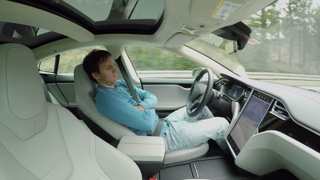 Male driver sleeping behind the self-driving steering wheel of an autonomous autopilot driverless car