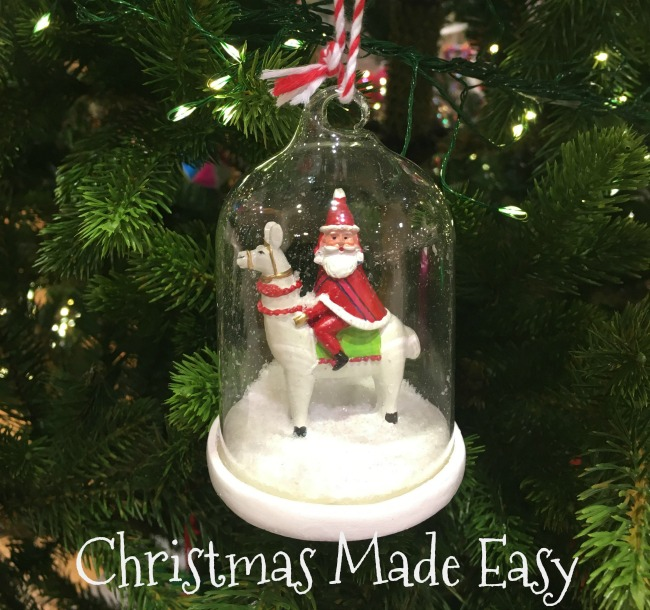 christmas-made-easy-text-under-image-of-tree-decoration-snow-globe-father-christmas-riding-a-llama
