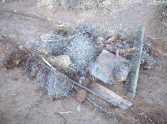 Dried yucca, lumber, sticks, and rocks gathered in a pile