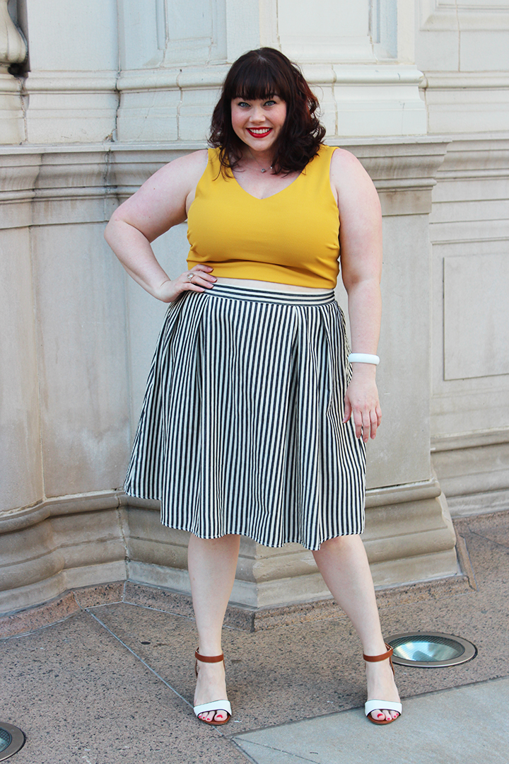 Plus Size Blogger Amber from Style Plus Curves Modeling one of the biggest plus size fashion trends of the summer -- the high-waisted skirt with a crop top. This pinstripe skirt and gold crop top are from Forever 21 Plus.