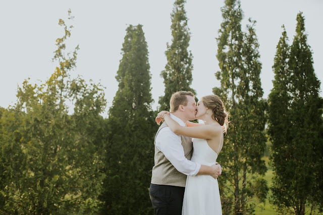 a bride and groom kiss in front of some shrubs
