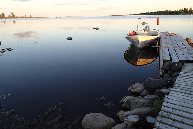 Rauhallinen merimaisema ilta-auringossa. Vene laiturissa.