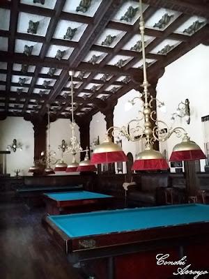Sala de billar con sus típicas mesas y lamparas de tres focos alumbrando sobre los tapices, bonito techo con artesonado de madera. Casino de Murcia