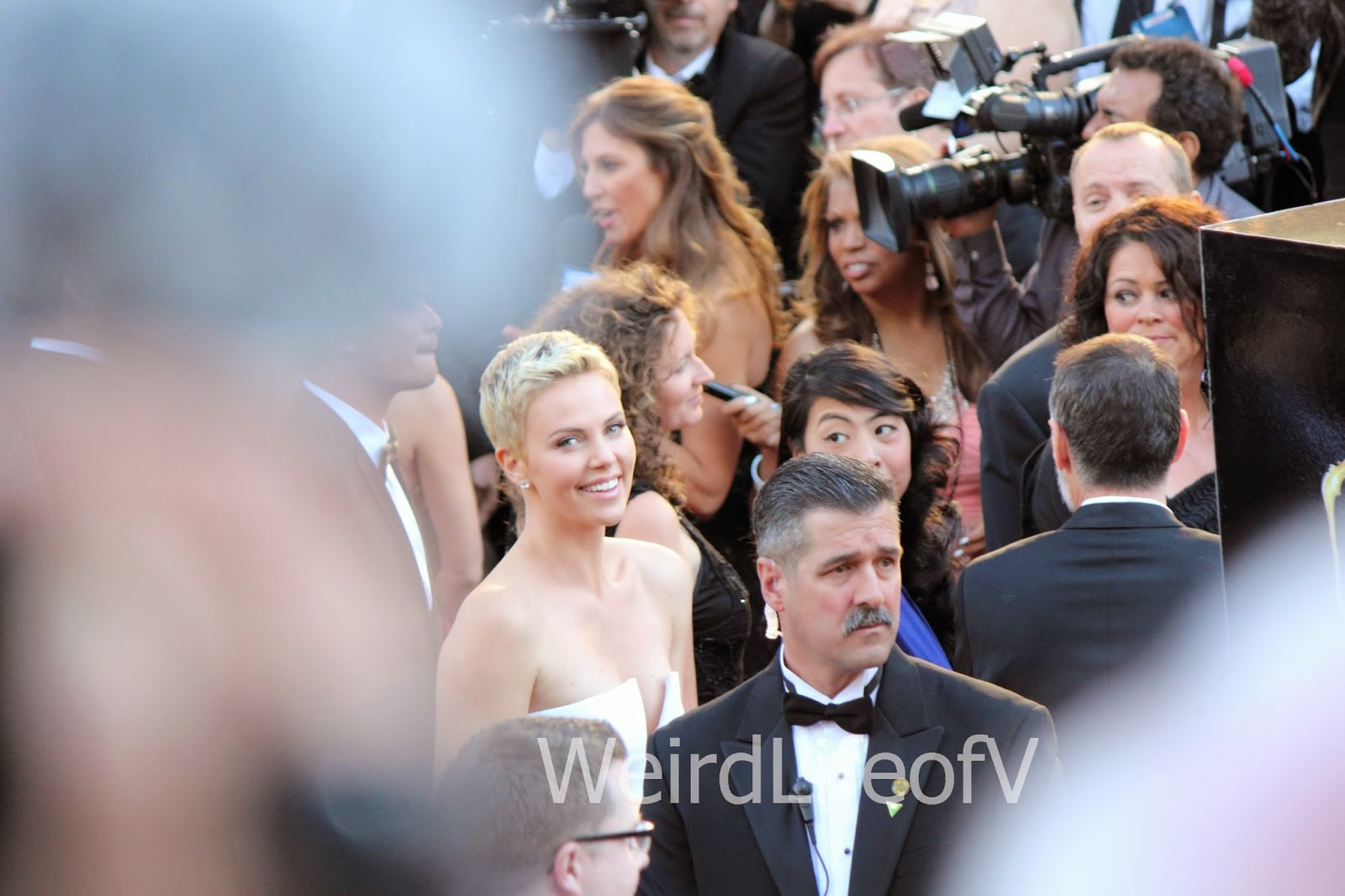 Charlize Theron smiling at the fans at the 2013 Academy Awards