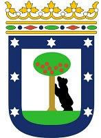 El escudo de Madrid con borde azul ancho que incluye las siete estrellas. El el centro, el oso apoya las patas delanteras en el tronco del madroño.