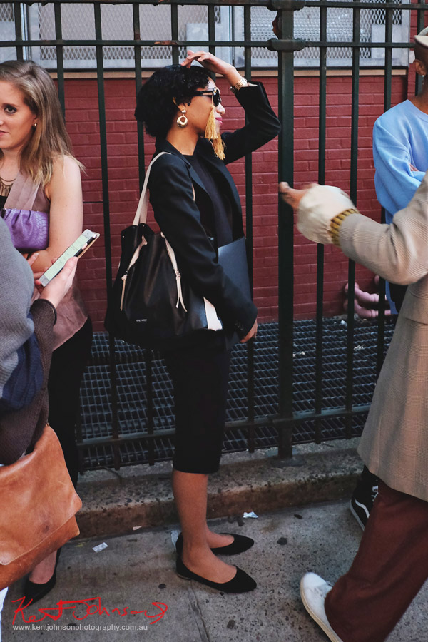 Woman in black skirt suit, bag and gold tasselled sunglasses. Street Fashion Sydney - New York Edition photographed by Kent Johnson