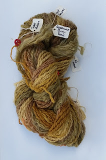 A hank of what looks like hand-spun fibres in varying shades of greens and browns. Light threads tied with red buttons have labels which are handwritten with the dye source and mordant.